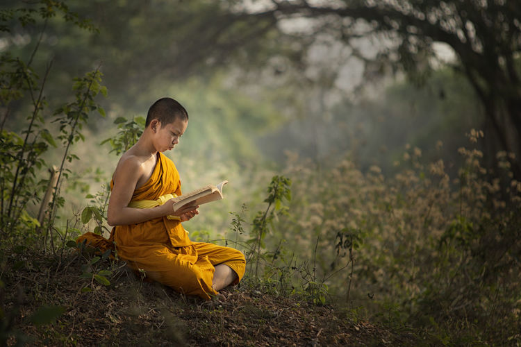 Monk reading book while sitting on field