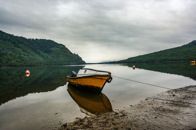 Boats In Calm Lake Against Cloudy Sky