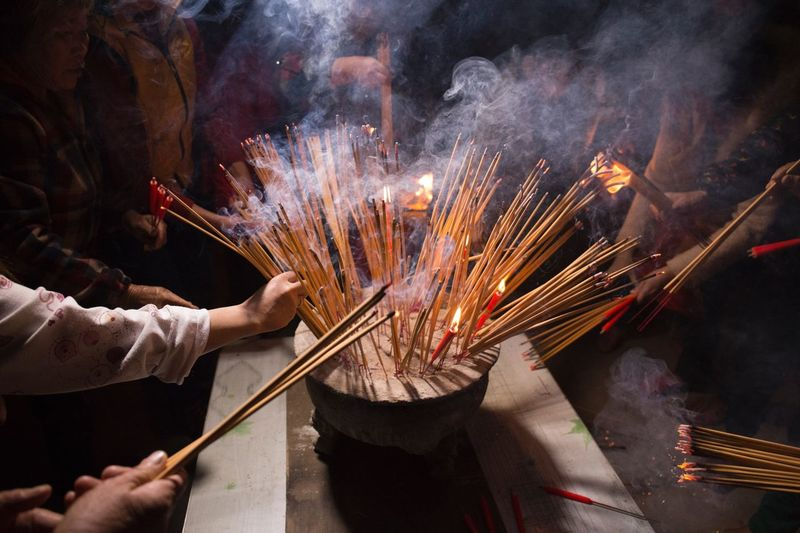 People burning incense sticks at temple