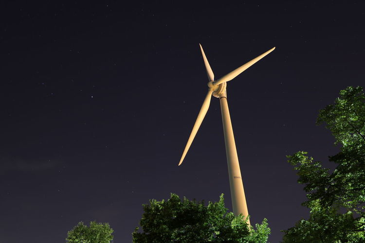 Low angle view of windmill against sky at night