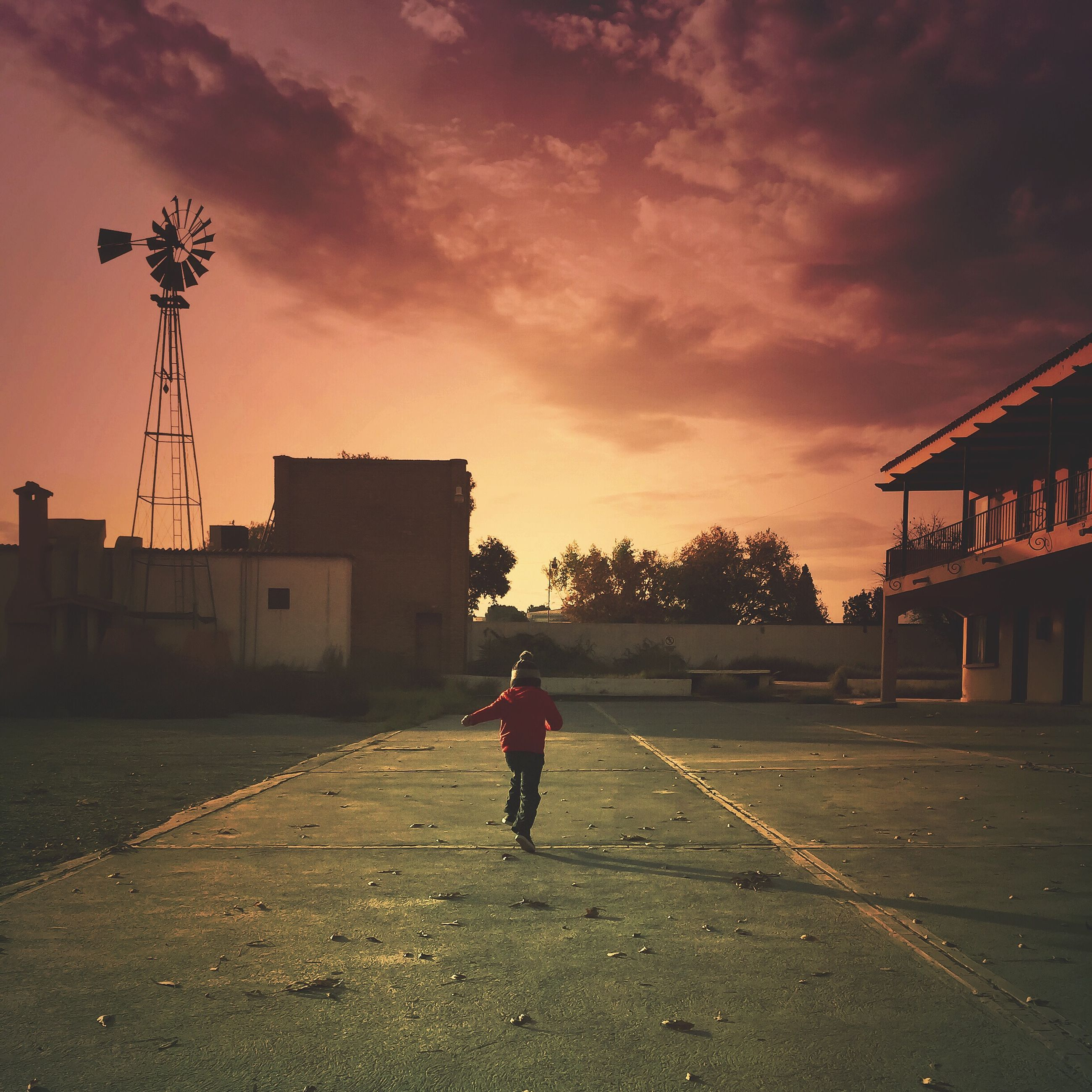 building exterior, sky, architecture, built structure, sunset, full length, lifestyles, street, walking, cloud - sky, rear view, leisure activity, men, road, the way forward, cloud, house, outdoors