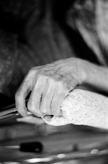 Cropped wrinkled hand holding railing