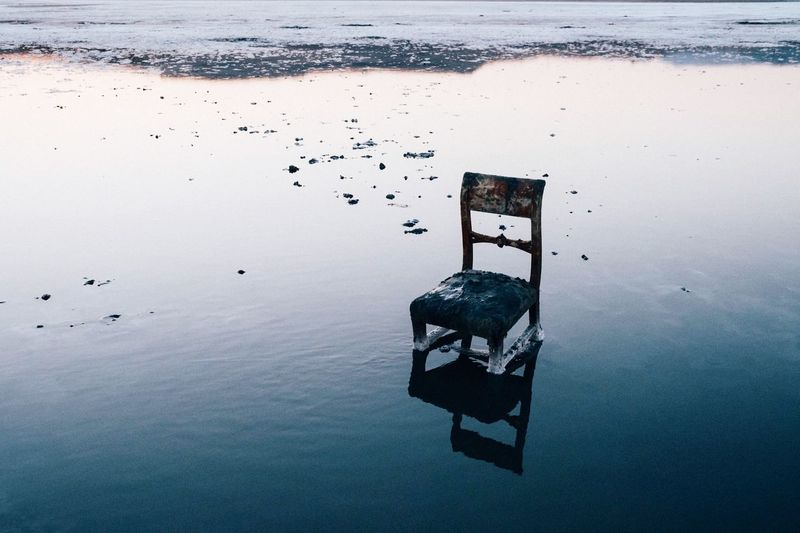 High angle view of weathered chair in sea