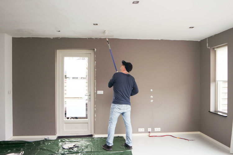 One Person Indoors  Casual Clothing Standing Day Home Interior Ceiling Renovating Maintenance New Home Painting Estate Do It Yourself Remodel Household Home Improvement Applying Painter Workman Handyman Paint Roller Brush Wall Ceiling Design Housepainting