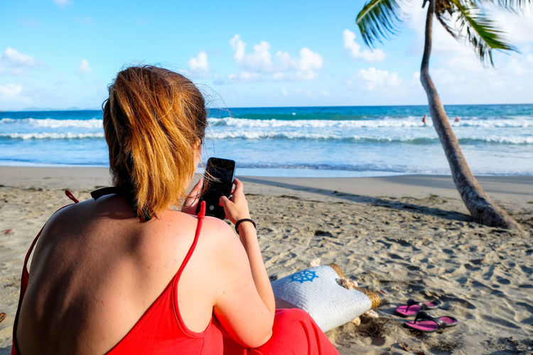 Sea Beach Land Water Technology One Person Nature Leisure Activity Beauty In Nature Rear View Photography Themes Lifestyles Real People Photographing Horizon Sky Adult Horizon Over Water Scenics - Nature Wireless Technology Outdoors Hairstyle Caribbean Tropical Island Travelling