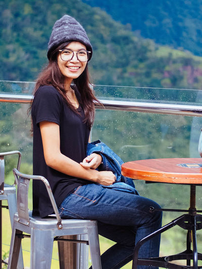 Portrait of smiling young woman sitting at table by railing
