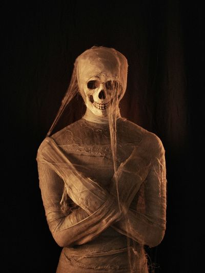 Mummy with skull over black background
