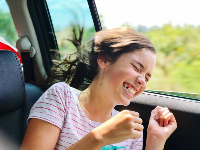 Car Transportation Land Vehicle Vehicle Interior Mode Of Transport Car Interior Day Real People One Person Young Adult Smiling Travel Leisure Activity Happiness Sitting Young Women Lifestyles Road Trip Vehicle Seat Outdoors Girl Wind Laugh Laughing Long Hair Fresh On Market 2017