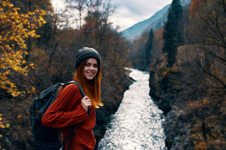 Young woman smiling in forest during autumn