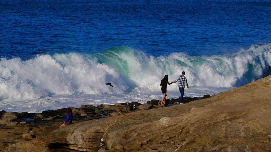 Couple walking on rock while sea waves rushing towards shore