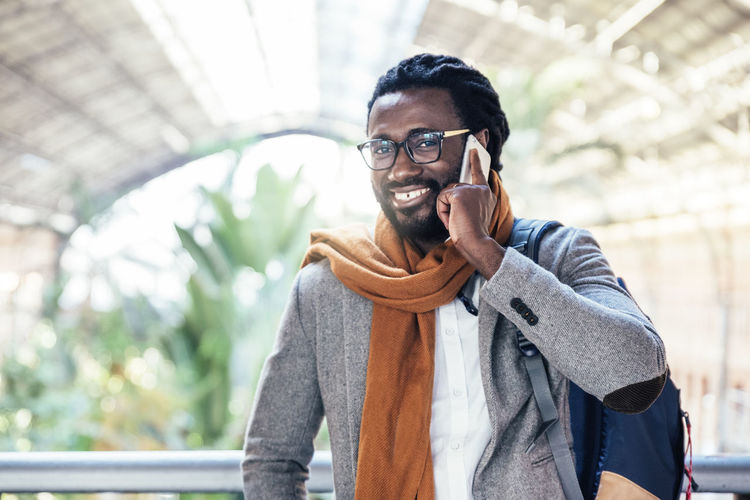 Portrait Of Smiling Man Talking On Mobile Phone In City