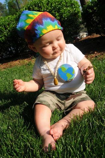 Baby girl sitting on grassy field