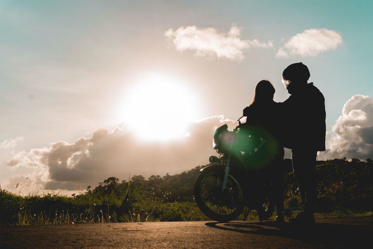 Low angle view of couple standing by motorcycle on land against sky