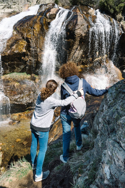 Mother and daughter looking at waterfall, rear view Adult Adventure Day Full Length Fun Hiking Leisure Activity Males  Men Motion Mountain Mountain Range Mountains Nature Outdoors People Real People Relaxing Rock Rock - Object Togetherness Two People Water Waterfall Waterfalls