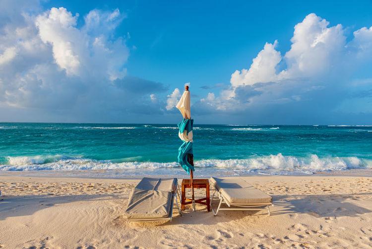 Sunchair on beach against sky