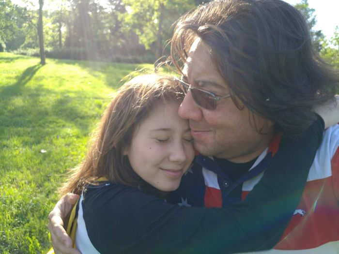 Girl embracing father on field in park