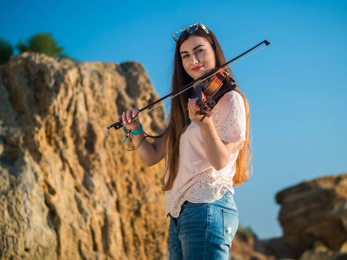 Portrait of young woman playing violin while standing against blue sky