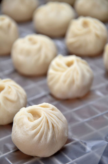Close-up of fresh homemade chinese dumplings on wax paper