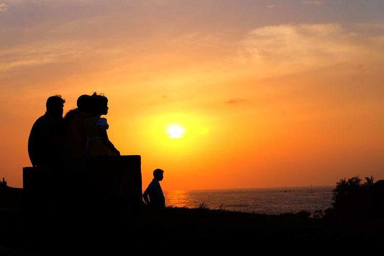 Silhouette people on shore against orange sky