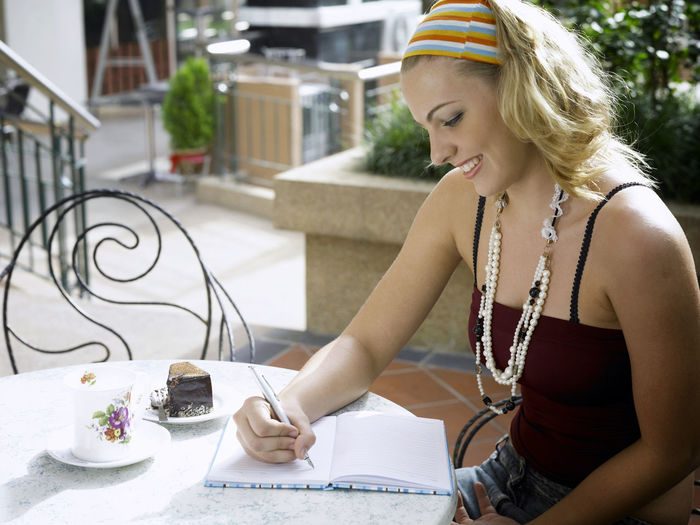 Young Woman Writing In Diary While Sitting At Table