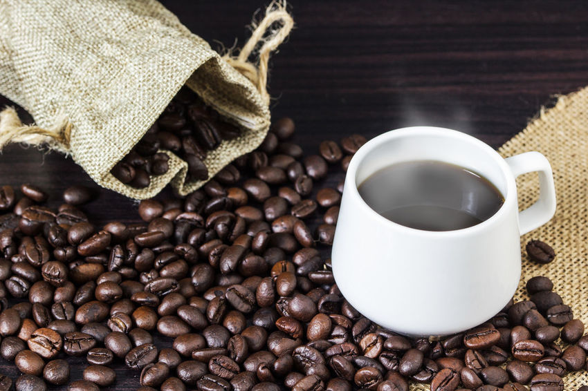 Cup of coffee with steam on table with coffee beans background. Americano Cafeine Coffee Coffee Time Espresso Hot Background Bag Bean Mug Relax Sack