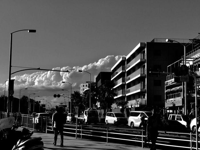 Man walking on road in city against sky
