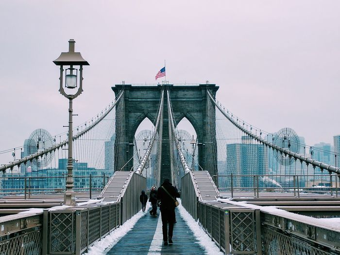 Rear view of people walking on brooklyn bridge