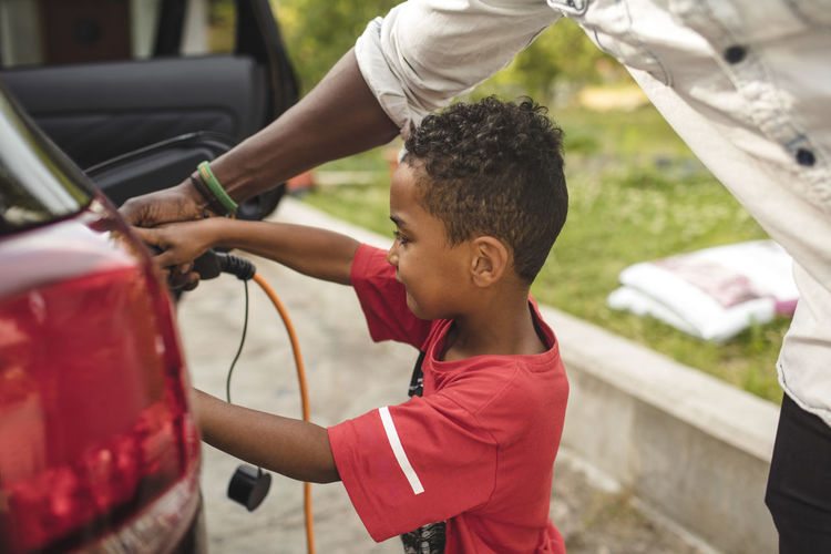 Side view of a boy holding a car