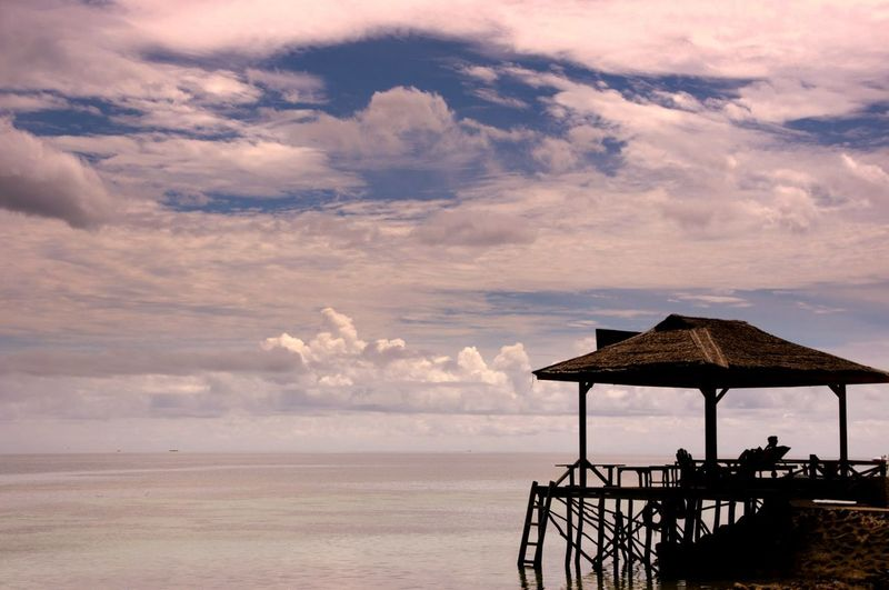 Thatched Hut By Sea Against Cloudy Sky