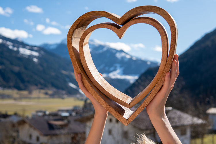 Cropped hands of woman holding heart shape against mountains