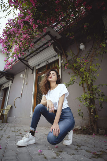Portrait of young woman sitting by building