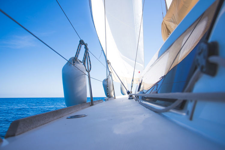 Close-up of sailboat sailing on sea against sky
