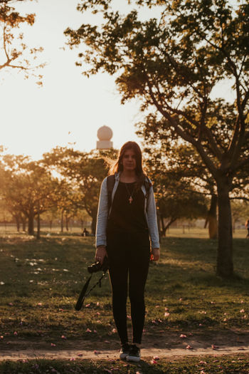 Full length of woman standing on field against trees