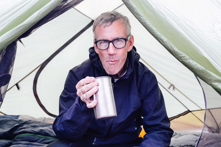 Man In Camping Tent Drinking From Tin Mug