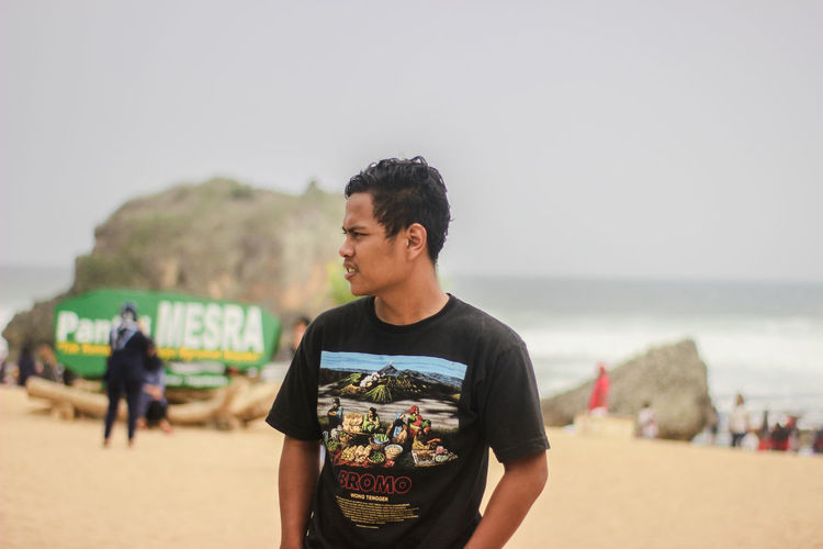 Man standing at beach against sky