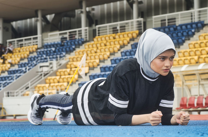 Sportswoman stretching and having some warming up before running One Person Real People Front View Sitting Indoors  Young Adult Hijab Factory Clothing Focus On Foreground Headscarf Industry Looking Casual Clothing Day Cap Concentration Adult Portrait Hood - Clothing