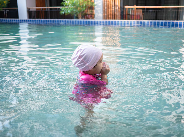 Side view of girl swimming in pool