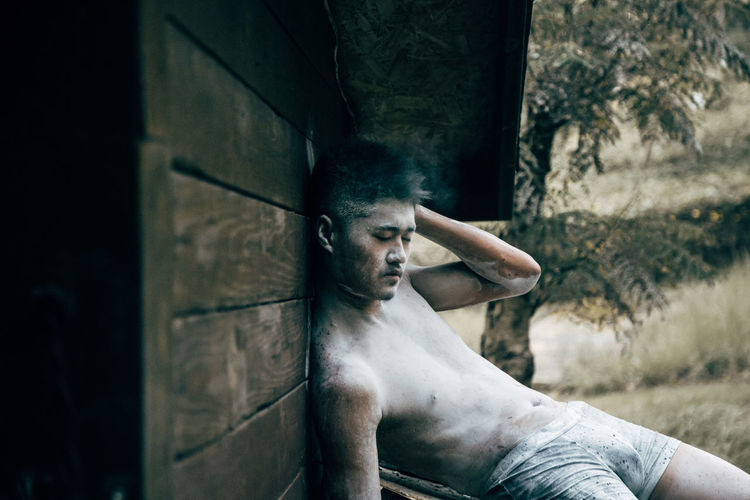 Young Man With Body Paint Relaxing Outdoors