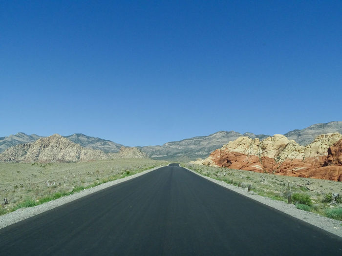 Empty road along landscape against clear blue sky