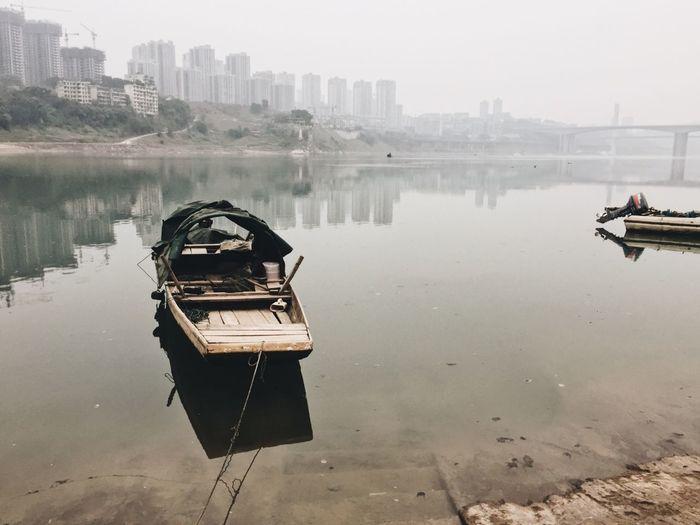 Boat in city against sky