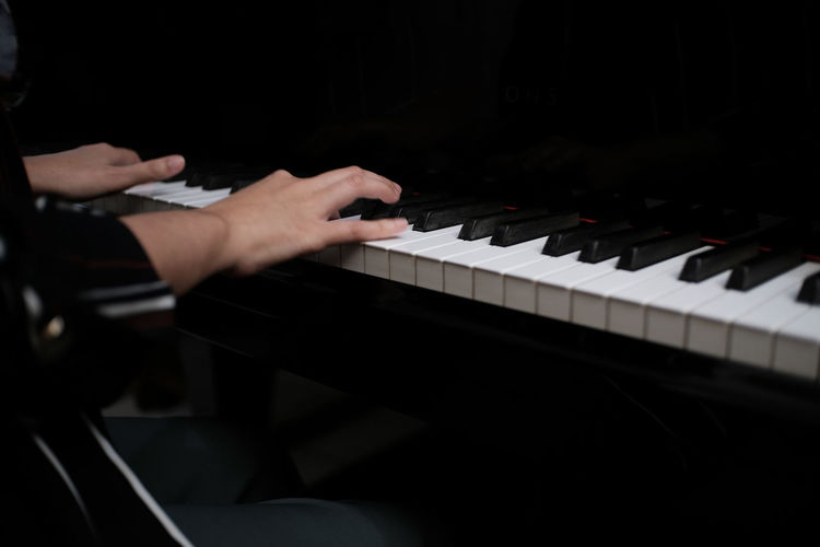 Cropped hand of man playing piano