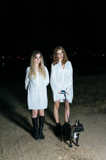 Full length portrait of female friends wearing white dress standing with dog on land at night