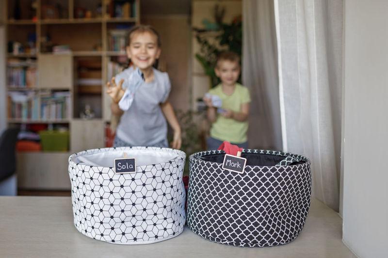 Cute kids throwing garment in basket on table