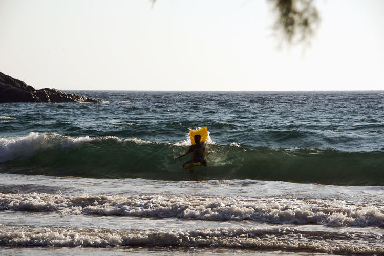 People playing, swimming in the waves in the island of Patmos, Greece in summer time Beauty In Nature Clear Sky Day Horizon Horizon Over Water Land Leisure Activity Lifestyles Motion Nature One Person Outdoors Rear View Scenics - Nature Sea Sky Standing Water Wave