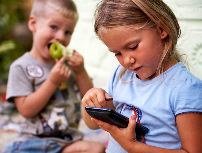 Close-Up Of Girl Using Phone While Sitting With Brother Outside