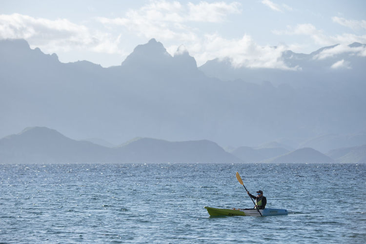 Man in boat on sea against mountains