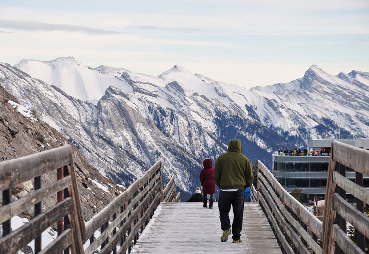 Rear view of people walking boardwalk against snowcapped mountains