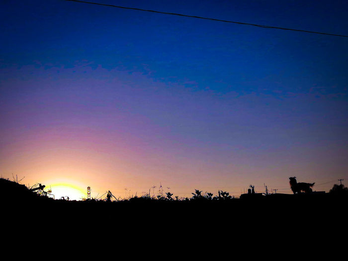 Silhouette landscape against clear sky at sunset