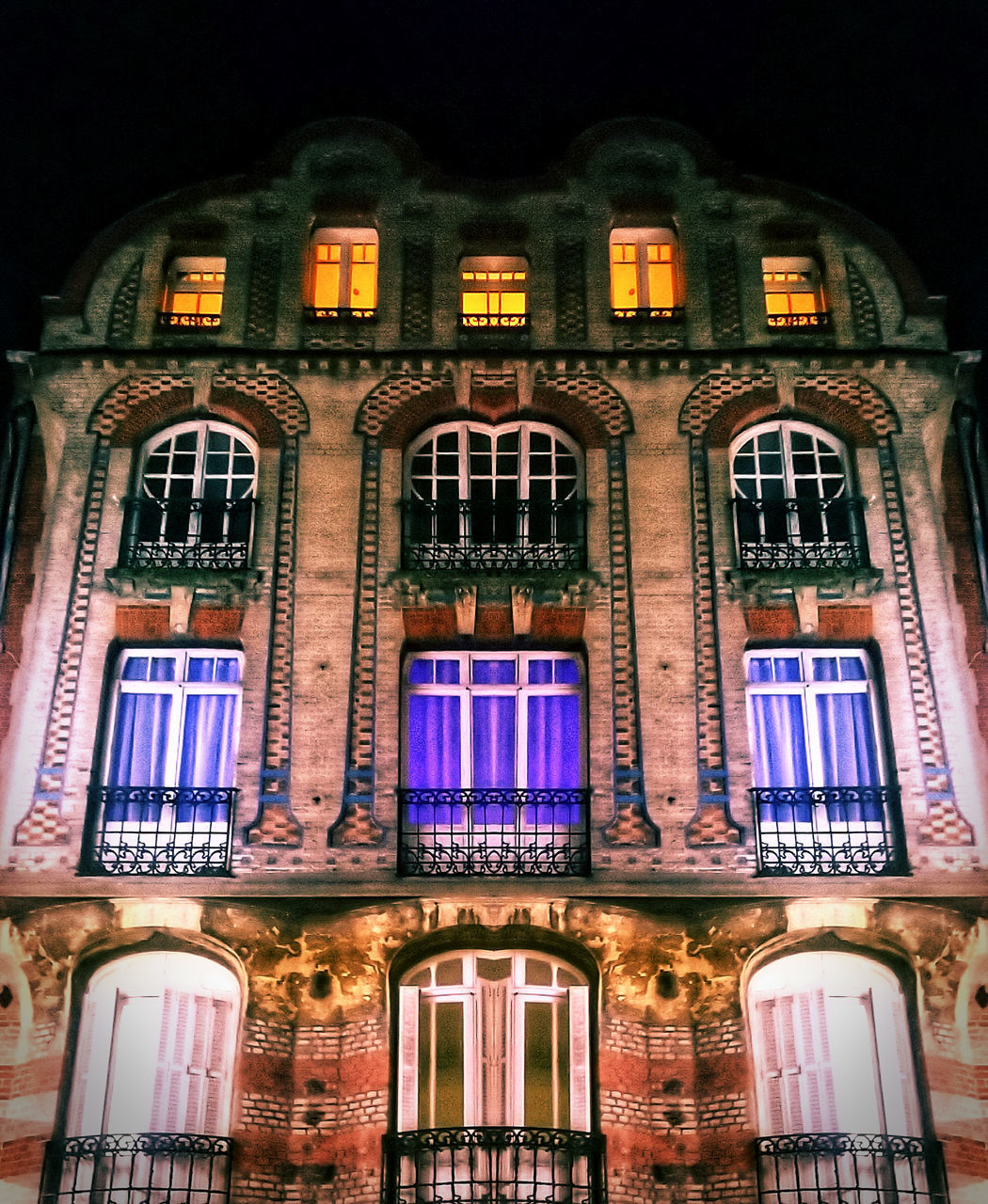 building exterior, architecture, illuminated, night, built structure, window, no people, low angle view, building, lighting equipment, history, the past, communication, residential district, glass - material, outdoors, pattern, city, facade, glowing, nightlife