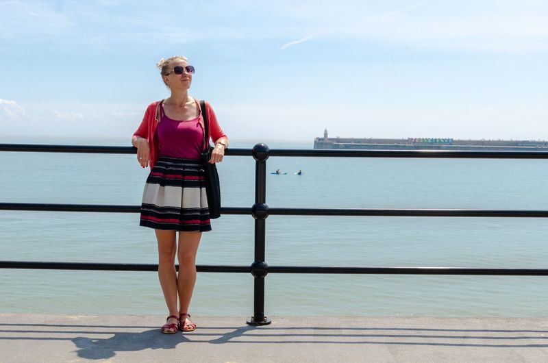 Full length of woman standing on pier over sea against sky